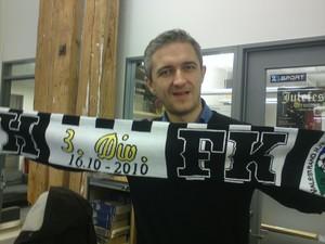 Aleksander Schau har VHFK skjerf på TV 2 kontoret.